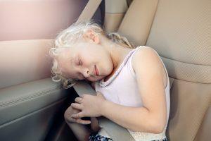 ילדה יושבת ברכב עם חגורת בטיחות
